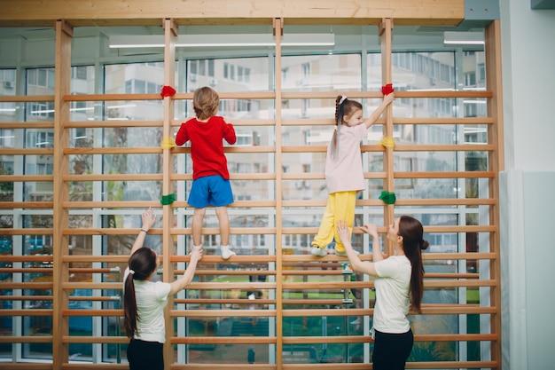 Dzieci w szwedzkiej ścianie ćwiczą na siłowni w przedszkolu lub szkole podstawowej z nauczycielami