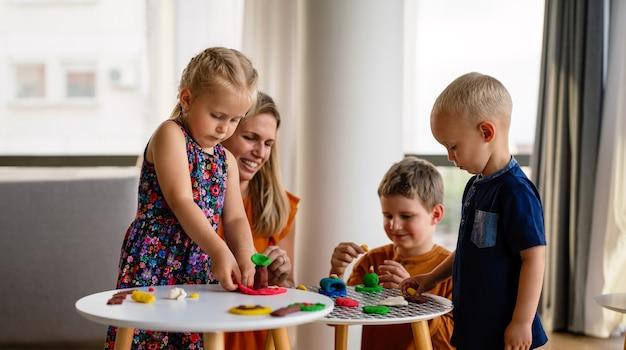 Dzieci w wieku przedszkolnym bawią się i bawią z nauczycielami. dziecko, koncepcja edukacji.