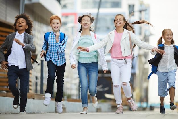 Dzieci w wieku szkolnym biegają razem na zewnątrz