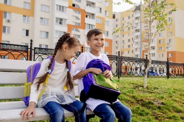 Dzieci w wieku szkolnym chłopiec i dziewczynka siedzą na ławce z jasnymi plecakami i uśmiechają się, patrzą w kamerę