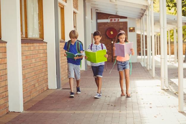 Dzieci w wieku szkolnym, czytając książki podczas spaceru w korytarzu