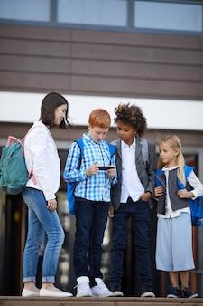 Dzieci w wieku szkolnym korzystające z telefonu