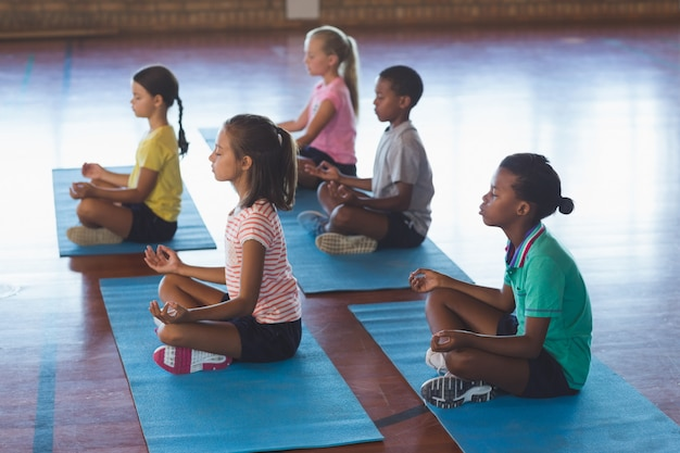 Dzieci w wieku szkolnym medytujące podczas zajęć jogi