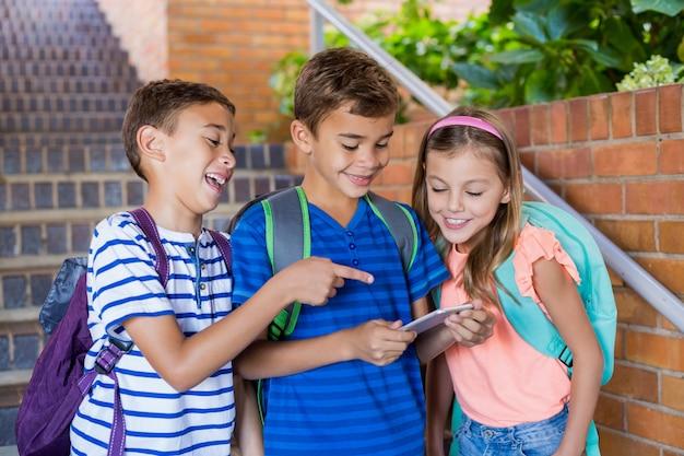 Dzieci w wieku szkolnym patrząc na telefon komórkowy