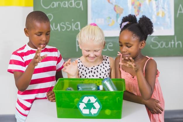 Dzieci w wieku szkolnym patrząc recyklingu logo pudełko w klasie