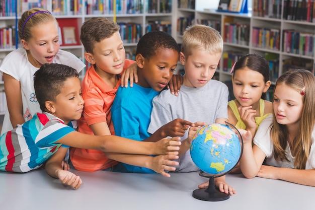 Dzieci w wieku szkolnym patrzeje kulę ziemską w bibliotece