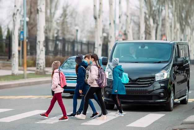 Dzieci w wieku szkolnym przechodzą przez ulice w maskach medycznych. dzieci chodzą do szkoły.
