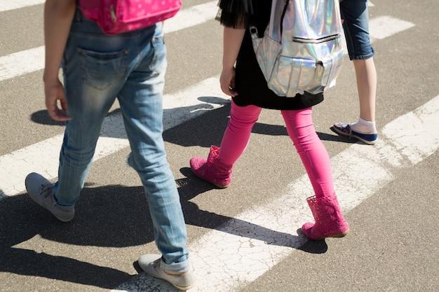 Dzieci w wieku szkolnym przechodzące przez jezdnię w drodze do szkoły
