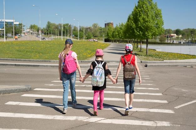 Dzieci w wieku szkolnym przechodzące przez ulicę w drodze do szkoły