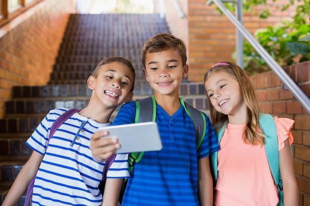 Dzieci w wieku szkolnym przy selfie z telefonu komórkowego