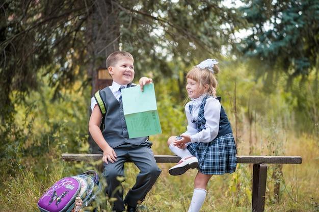 Dzieci w wieku szkolnym siedzą na ławce z teczkami i zeszytami.