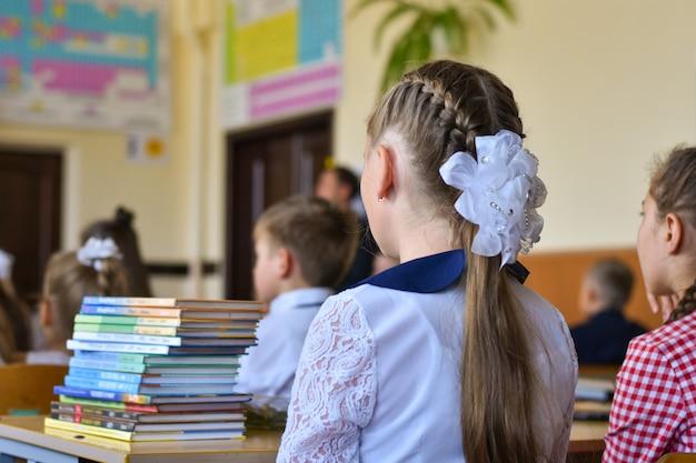 Dzieci w wieku szkolnym siedzą przy biurkach w klasie szkoły