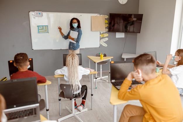 Dzieci w wieku szkolnym siedzą przy swoich ławkach podczas lekcji
