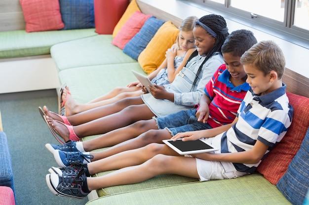 Dzieci w wieku szkolnym siedzi na kanapie i używa cyfrową pastylkę w bibliotece