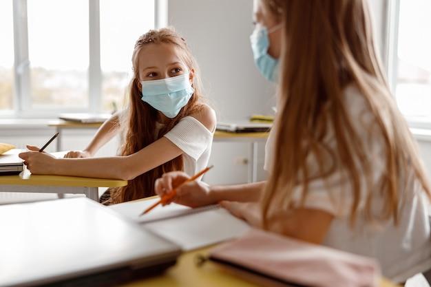 Dzieci w wieku szkolnym trzymające ołówki i używające zeszytów w klasie