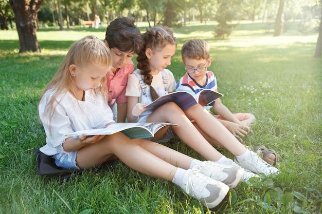Dzieci w wieku szkolnym uczące się na świeżym powietrzu na trawie w parku ublic