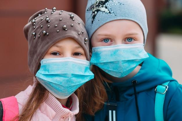 Dzieci w wieku szkolnym w maskach medycznych. portret dzieci w wieku szkolnym.