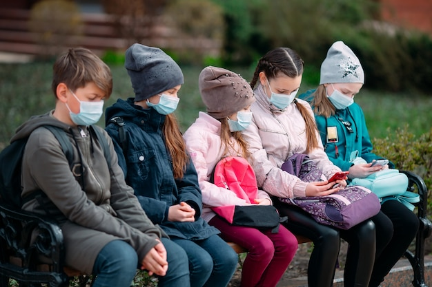 Dzieci w wieku szkolnym w maskach medycznych siedzą na ławce.