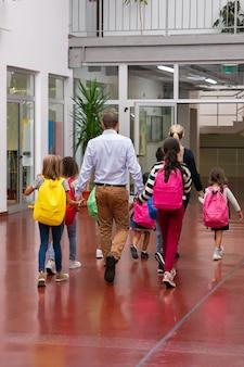Dzieci w wieku szkolnym z jasnymi plecakami przechadzające się po szkolnym korytarzu, trzymając się za ręce nauczycieli