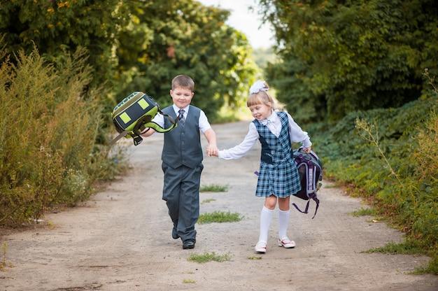 Dzieci w wieku szkolnym z teczkami biegną do szkoły. pierwsi równiarki