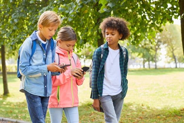 Dzieci w wieku szkolnym z telefonami komórkowymi
