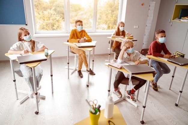Dzieci w wieku szkolnym z zeszytami siedzą razem w klasie