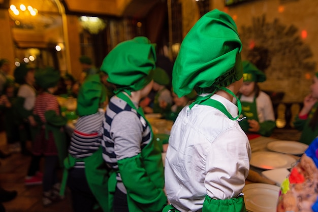 Dzieci w zielonych garniturach kucharzy i zielonych czapek stoją w rzędzie