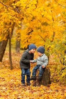 Dzieci w żółtym i złotym lesie jesienią