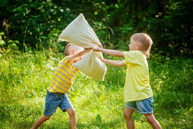 Dzieci walczą razem z poduszkami w słonecznym letnim ogrodzie
