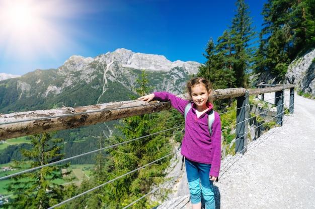 Dzieci wędrują w piękny letni dzień w alpach austrii, odpoczywając na skale i podziwiając niesamowity widok na szczyty górskie. aktywny wypoczynek rodzinny z dziećmi. zabawa na świeżym powietrzu i zdrowa aktywność