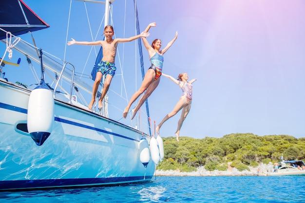 Dzieci wskakują do morza żaglowego jachtu podczas letniego rejsu. przygoda w podróży, żeglarstwo z dzieckiem na rodzinnych wakacjach.