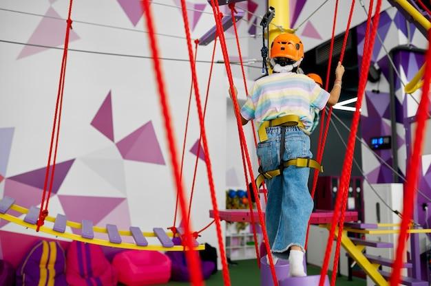 Dzieci wspinają się na tyrolkę w centrum rozrywki, mali wspinacze. chłopiec i dziewczynka bawią się na linach w strefie wspinaczkowej, dzieci spędzają weekend na placu zabaw, szczęśliwe dzieciństwo