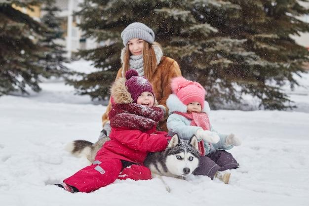 Dzieci wychodzą i bawią się z psem husky w zimie. dzieci siedzą na śniegu i głaskają psa husky. spaceruj po parku zimą, radość i zabawa, pies husky o niebieskich oczach. , gru