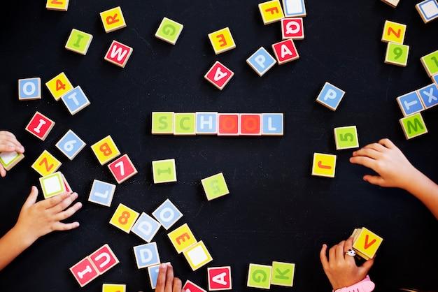Dzieci, Wypowiadanie Słów Z Bloków Alfabetu Premium Zdjęcia