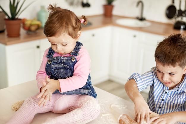 Dzieci wyrabiają ciasto siedząc na kuchennym stole