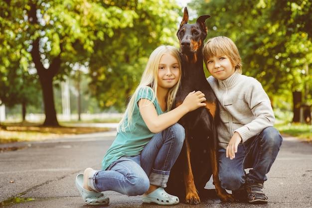 Dzieci z dobermanem w letnim parku.