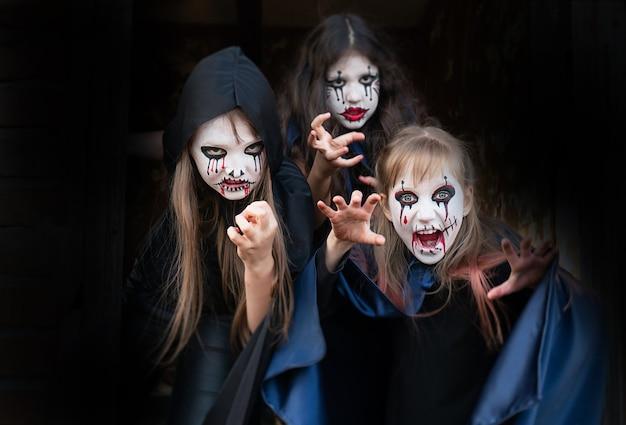 Dzieci z farbami do twarzy i kostiumami na halloween