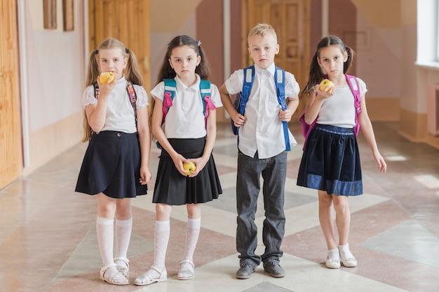 Dzieci z jabłkami stoi w szkolnym korytarzu