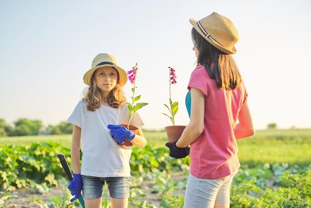 Dzieci z kwiatami w doniczkach, rękawiczki z narzędziami ogrodniczymi