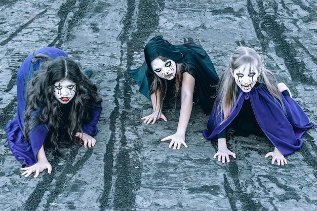 Dzieci z malowaniem twarzy i kostiumami na halloween na dachu opuszczonego budynku