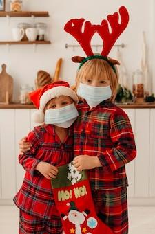 Dzieci z maską medyczną trzymające skarpetę świąteczną