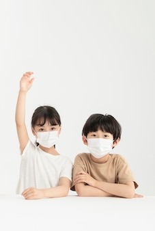 Dzieci z maską ochronną podnoszącą rękę