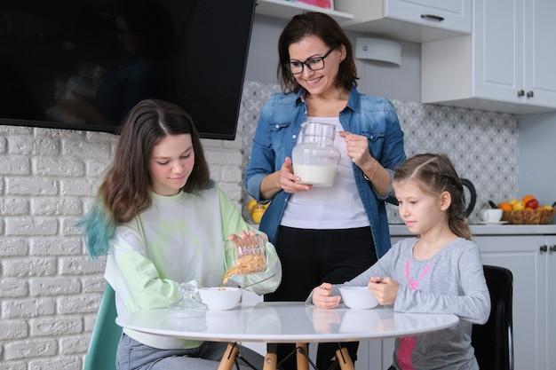Dzieci z matką jedzące w domu w kuchni, dwie dziewczyny siedzące przy stole z talerzami płatków kukurydzianych i mleka. rodzina, jedzenie, komunikacja, koncepcja zdrowia.