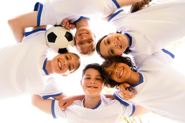 Dzieci z niskim kątem w sportowej odzieży patrzą w dół