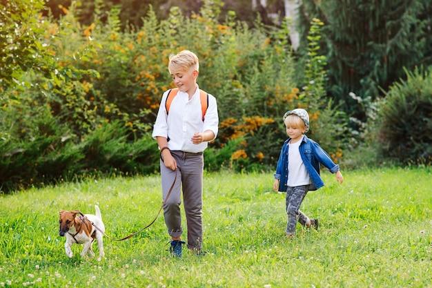 Dzieci z psem na spacerze w parku. rodzina, przyjaźń, zwierzęta i styl życia. dzieci z psem jack russel terrier na zewnątrz. szczęśliwi chłopcy bawić się z psem na zielonej trawie.