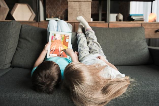 Dzieci z tabletem na kanapie