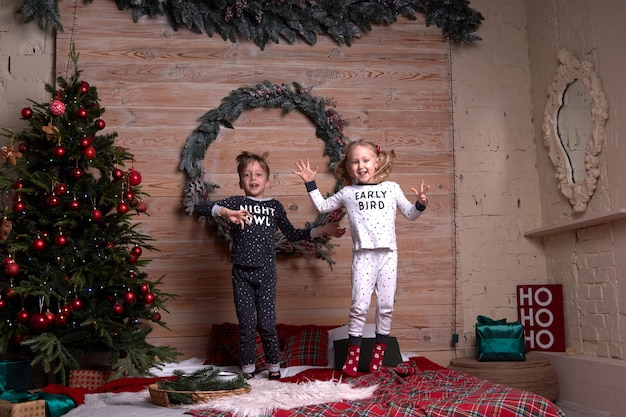 Dzieci z tej samej rodziny wyglądają na miękkie, ciepłe piżamy bawiące się w domu w świąteczny wieczór pod udekorowaną choinką. szczęśliwy dzieciak skacze na łóżku. święta nowego roku.