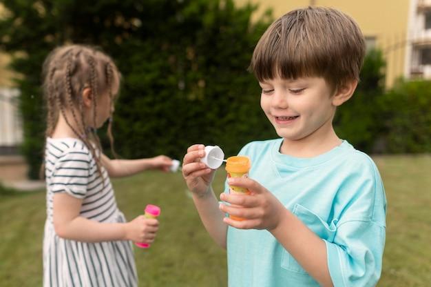 Dzieci z urządzeniem do wytwarzania baniek mydlanych