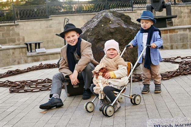 Dzieci z walizkami podróżują, ubrania na wiosnę retro. małe dziecko siedzi na walizce i czeka na autobus.