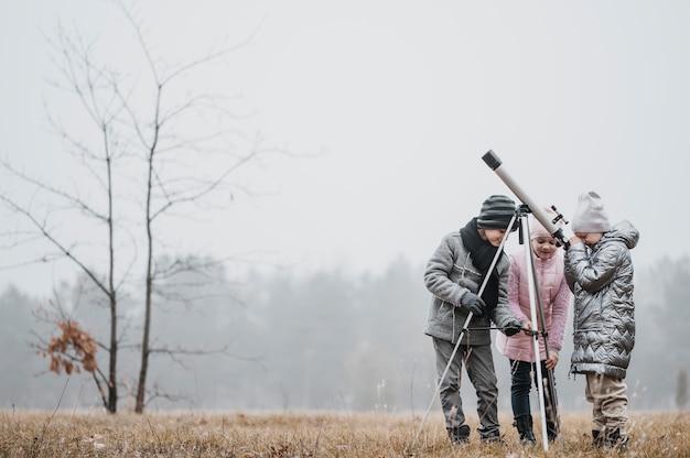 Dzieci za pomocą teleskopu na zewnątrz z miejsca na kopię